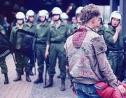 A punk faces a line of riot police.